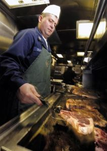 A cook flips a slab of beef on the grill.